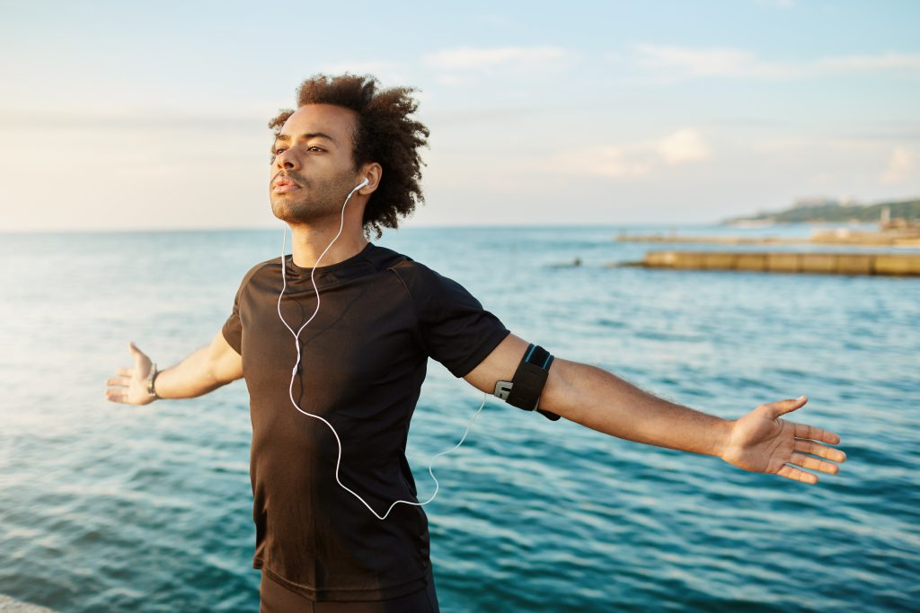 man beside the sea, breathing in during yoga sesssion